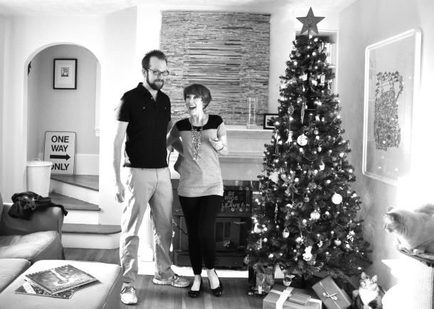 """A photo taken of the Professor and I for his parents required (and embarrassing) Christmas letter. I am sporting """"regular pants"""" from Ann Taylor that are NOT AT ALL COMFY anymore and a rocking maternity sweater from Gap that I grabbed on super clearance. The Professor is in a Banana Republic Polo and slacks that were on deep clearance. This is about as normal a photo as we take. :)"""